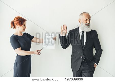 Woman Holding Business Contract And Businessman Refusing To Sign It
