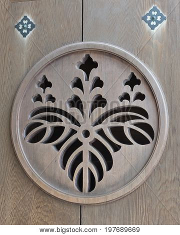 Close up of the detail of a shrine door with leaf and flower motif.