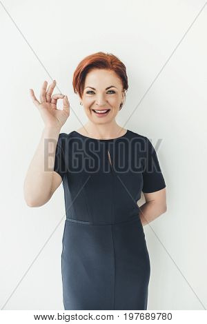 Happy Mature Woman Showing Okay Sign On White Background