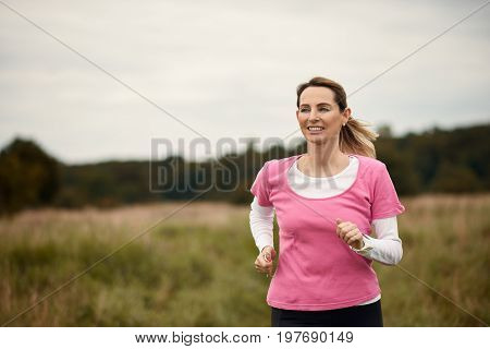 Cheerful woman running through field in fall copy space to the left