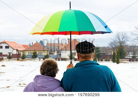 Walking elderly couple in the park in wintertime