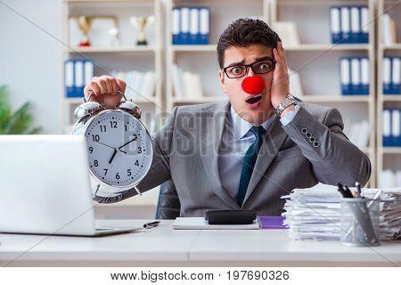 Clown businessman with alarm clock missing dieadline