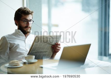 Seerious man reading vacancy adverts in newspaper