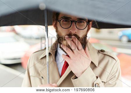 Posh man smoking under umbrella
