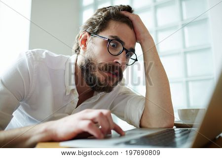 Nervous job-seeker sitting in front of laptop