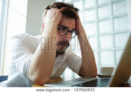 Worried man looking at laptop display