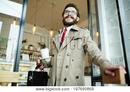 Young businessman with briefcase and drink leaving cafe