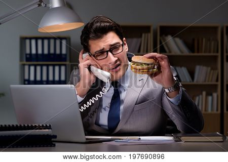 Businessman late at night eating a burger
