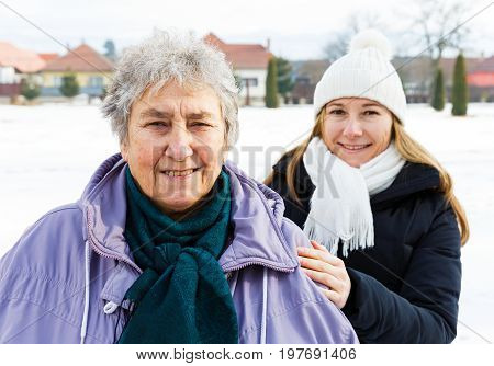 Photo of happy elderly woman and young caregiver