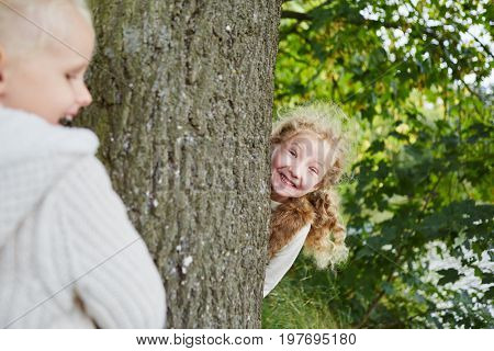 Two girls playing hide and seek in autumn at the park