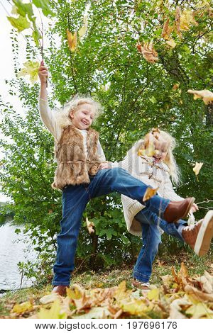 Two kids playing at the park in autumn romping and moving around