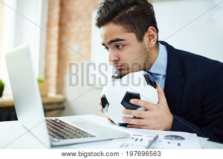 Young economist with soccer ball watching football match in front of laptop