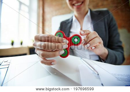Businesswoman with fidget spinner having anti-stress timeout