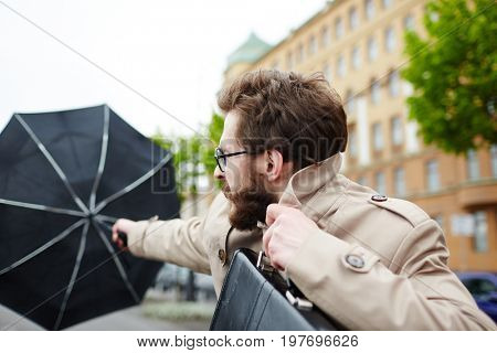 Businessman with umbrella confronting wind while going to work