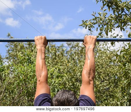 Hands On The Bar Close-up. The Man Pulls Himself Up On The Bar. Playing Sports In The Fresh Air. Hor