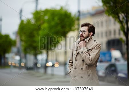 Young man in trenchcoat waiting for taxi in rainy weather
