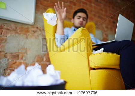Young man with laptop throwing paper-ball into trash bin