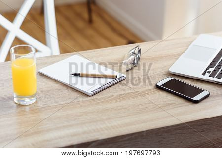 Notepad, Laptop, Smartphone And Glass Of Juice On Table In Home Office