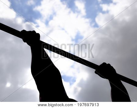 Silhouette Of Hands On A Horizontal Bar. Hands On The Bar Close-up. The Man Pulls Himself Up On The