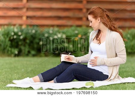 Happy Beautiful Pregnant Woman Writing In Diary Wile Sitting On Green Lawn