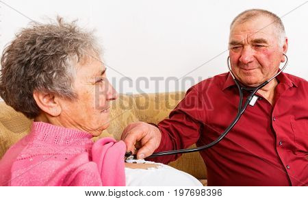 Photo of elderly man listening his wife heartbeat