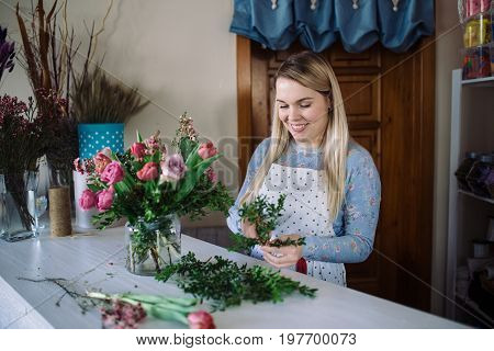 woman florist making bouquet of flowers indoor. Female florist preparing bouquet with roses tulip in flower shop