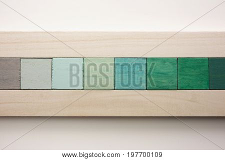 abstract title back with colored wooden blocks between natural colored wood, isolated on white. grey to green.