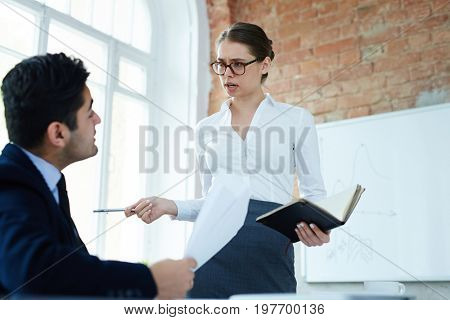 Strict woman talking to her subordinate or colleague