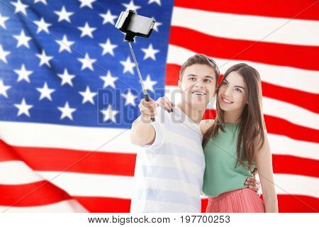 Young couple tacking selfie and USA flag on background
