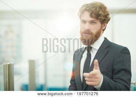 Portrait of successful young businessman winking at camera confidently and pointing to the viewer