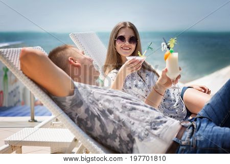 Male and female relaxing on a chaise-lounges on a blue sea background. Pretty girl in a sunglasses with long brown hair. A confident man having fun on a beach. A happy couple on a summer holiday.