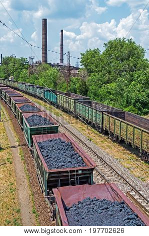 Cargo wagons with coke on the railway tracks leading to metallurgical enterprise of blast furnace smelting