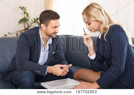 Businessman flirting with young blonde businesswoman in office