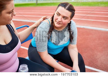 Young over-size woman supporting her friend after difficult workout
