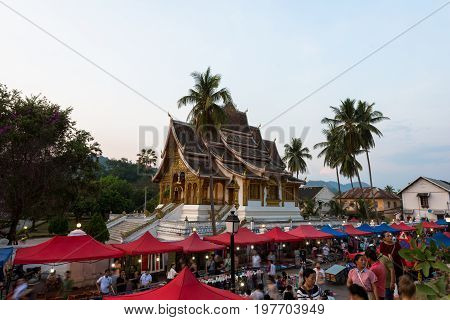 LUANG PRABANG LAOS - MARCH 11 2017: From outside wide angle picture of Haw Pha Bang located on the grounds of the Royal Palace Museum in Luang Prabang Laos. Beginning of night market.