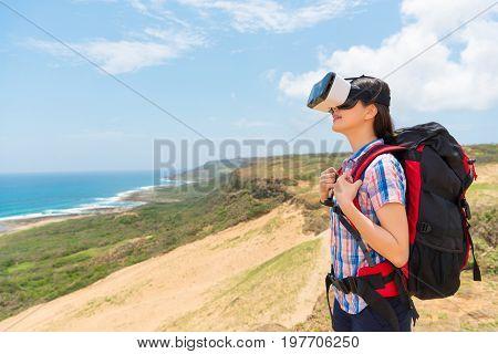 Smiling Female Backpacker Wearing Virtual Reality