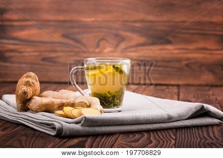 A bright cup filled with hot herbal tea on a light brown wooden background. A little cup of delicious and healthy tea next to pieces of ginger. A traditional ginger and lemon tea on a gray fabric.