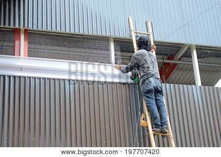 Worker Climbing Bamboo Stair Installation Wiremesh And Translucent Louver In Construction Site