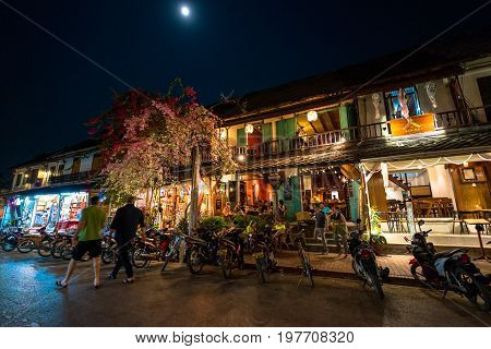 LUANG PRABANG LAOS - MARCH 11 2017: Wide angle picture of people inside of coffee shops and restaurants at Sisavangvong Road located in the olf Quarter of Luang Prabang Laos.