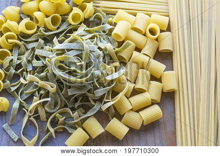 Several sorts of raw green and yellow pasta are on the wooden background