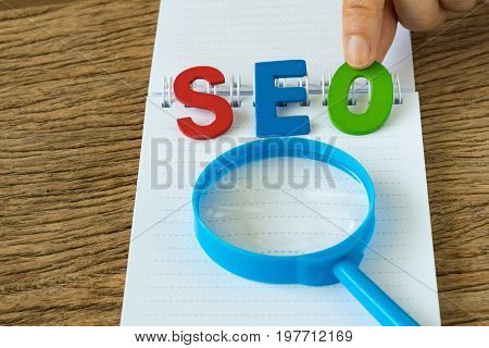 SEO Search engine optimisation concept as hand holding colorful alphabet abbreviation SEO with magnifying glass on white paper on the wooden table.