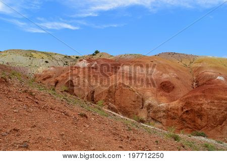 Red cliffs of red hills in Altai mountains. Martian landscape. Altay Republic Russia.