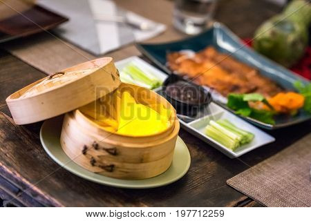 Chinese Cuisine Food - Peking Duck with yellow pancakes in wood crate and vegetables at Rome, Italy.