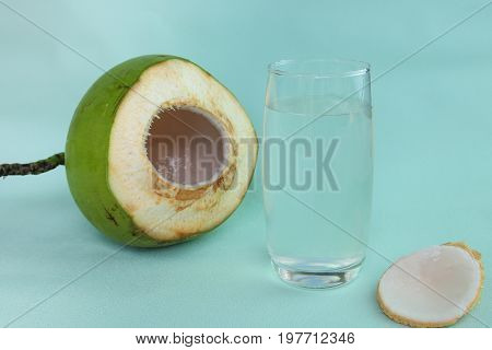 Fresh  coconut water in glass Ready to drink on pastel green background, summer and healthy concept.