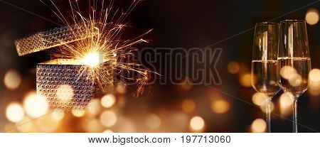 Sparkling surprise gift with golden bokeh and champagne for wedding or christmas