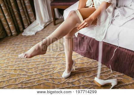 Unrecognizable bride in a silk robe with beautiful slim legs is putting on stockings. Wedding morning preparation. Dressing lingerie boudoir.