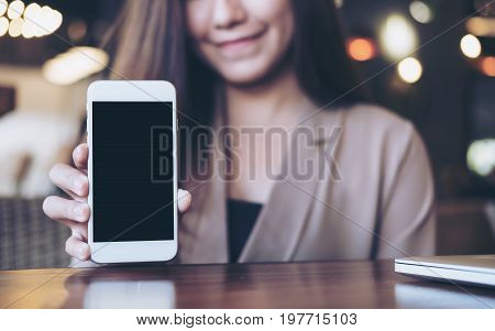 Mockup image of a beautiful Asian business woman holding and showing white mobile phone with blank black screen in cafe