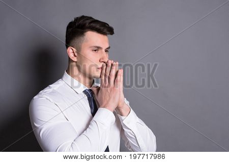 Successful businessman. Pensive young man standing at gray studio background