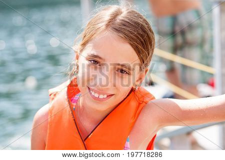 Happy teenage girl in orange life vest at the beach vacation