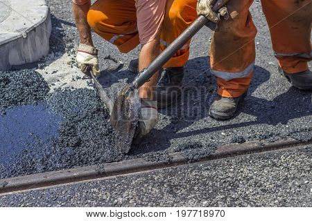 Workers Using A Shovel To Spread Mastic Asphalt